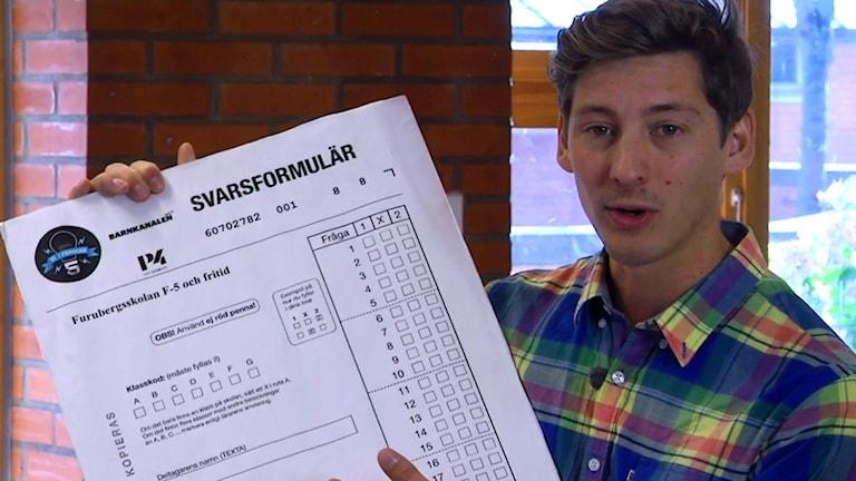 Programledaren Kim Ohlsson med en förstorad variant av svarsformuläret. Blankett. Foto: SVT Play.