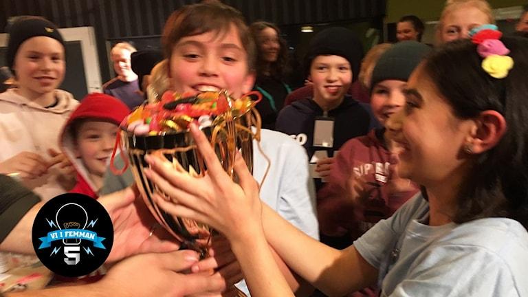 Vinnarna från Lackarebäcksskolan i P4 Göteborg håller pokalen som är fylld med godis.