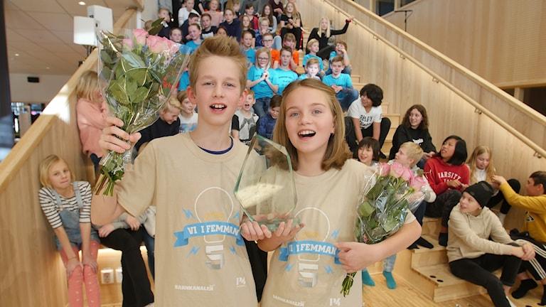 Valdemar och Hanna har blommor och en glasstaty i handen och ser glada ut.