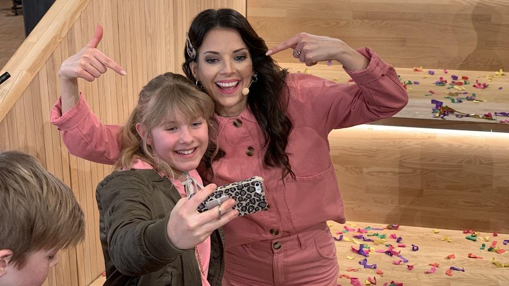 Programledaren Malin Olsson tar en selfie tillsammans med en elev.