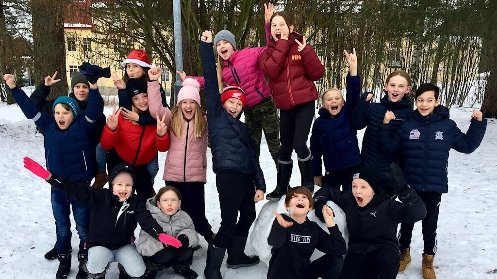 Klass 5:4 på Mimerskolan i Sundsvall jublar med uppsträckta armar på skolgården. Foto: Karin Lönnå/Sveriges Radio