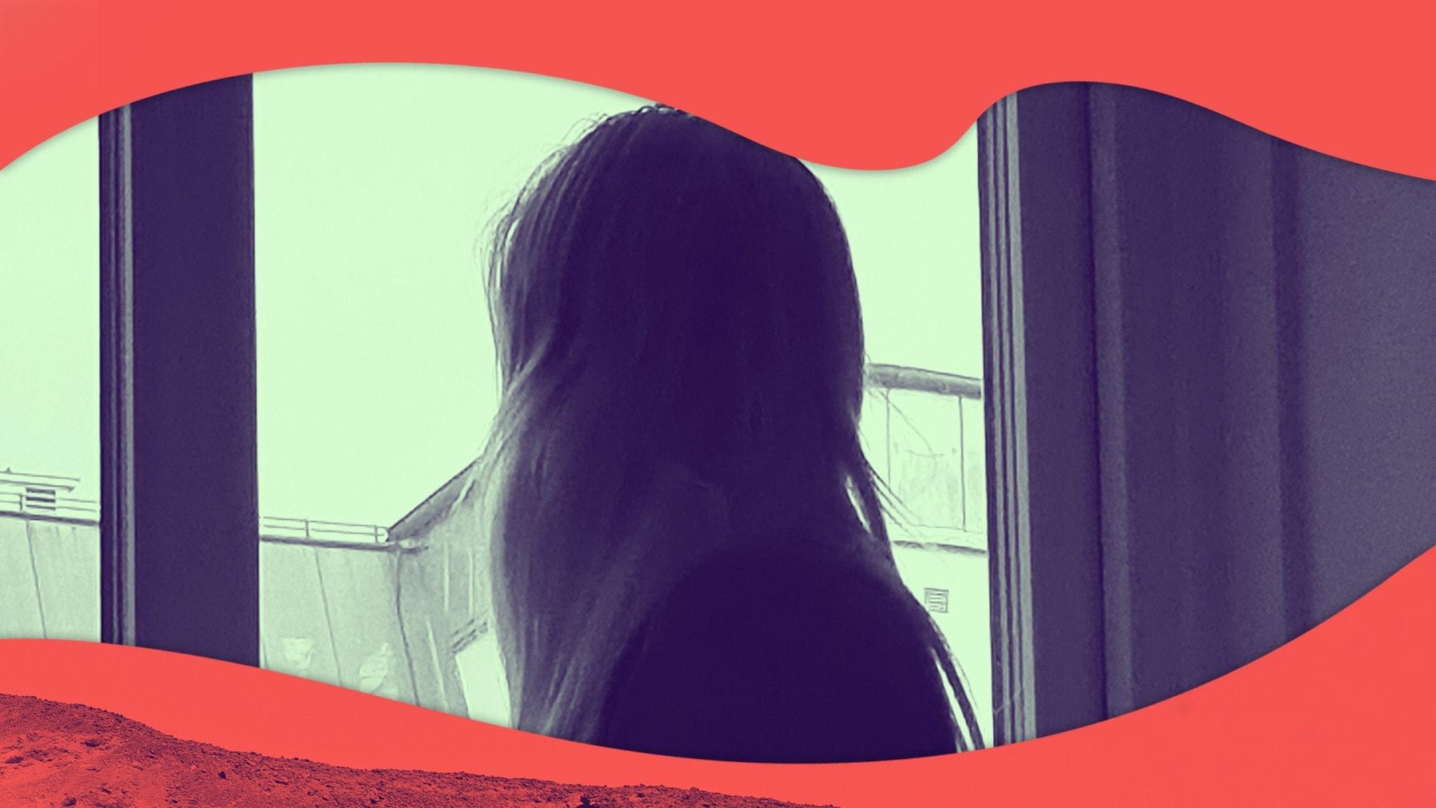 Anna sitter vid ett fönster med blicken vänd utåt.