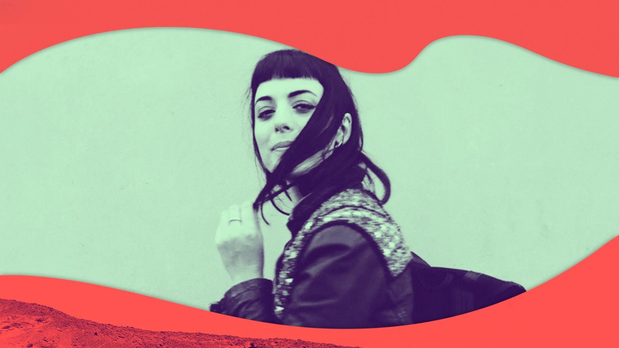 Maja står mot en vägg, pillar lite med håret och tittar in i kameran.