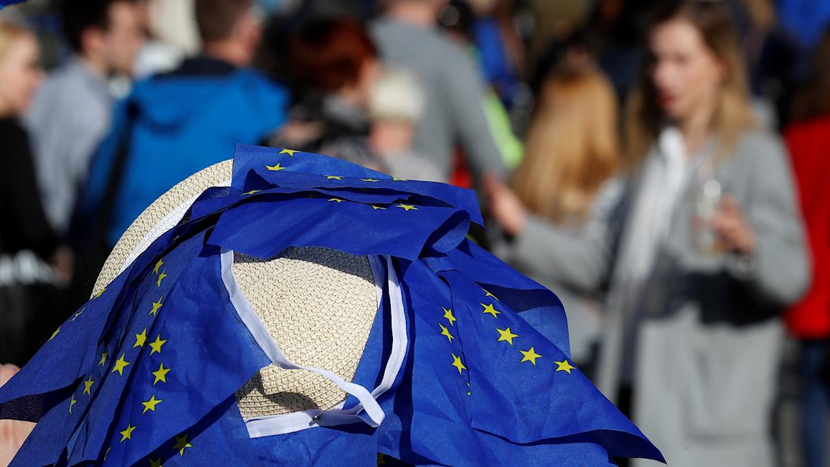 EU-flaggor och människor i rörelse.