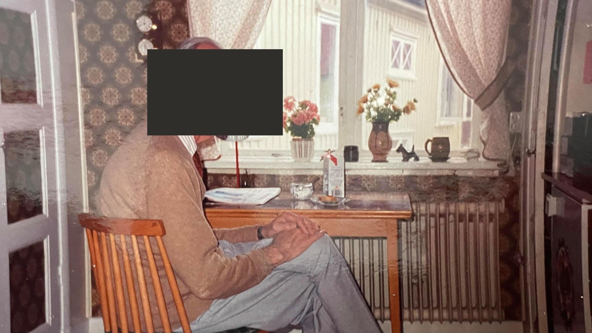En äldre man sitter vid ett köksbord med ett mjölkpaket och en tidning framför sig. Ögonen är maskade.