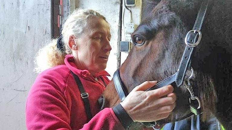 Marita blundar och håller om hästen Ladys huvud.