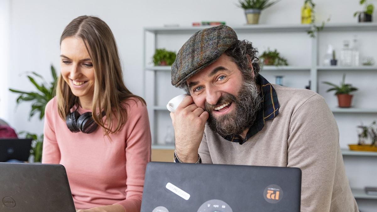 En kvinna och en man sitter vid varsin dator.