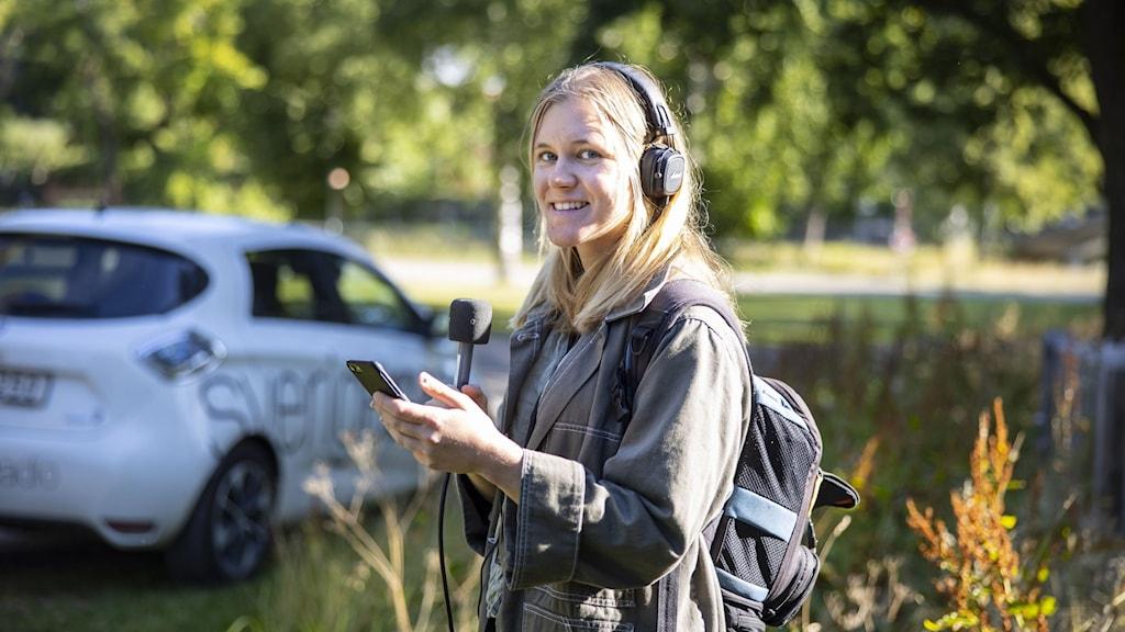Reporter med mikrofon och OB-väska i solen med Sveriges Radio-bil i bakgrunden.