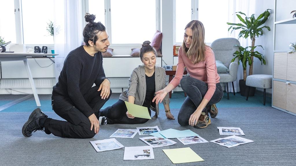 Tre personer sitter på golvet och planerar.