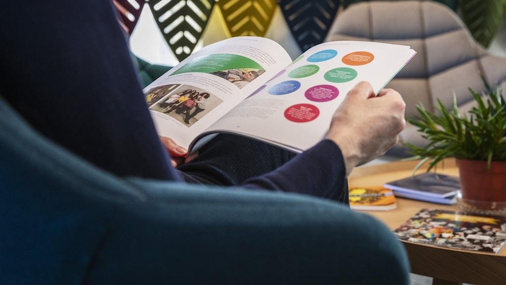 Någon läser en broschyr