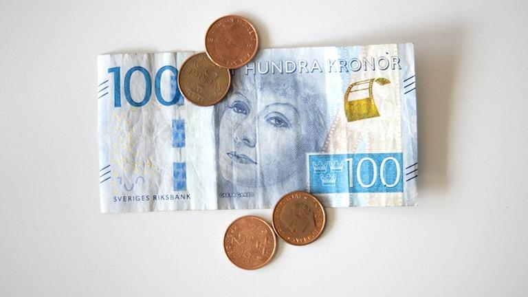 Bild på en hundralapp och fyra mynt.
