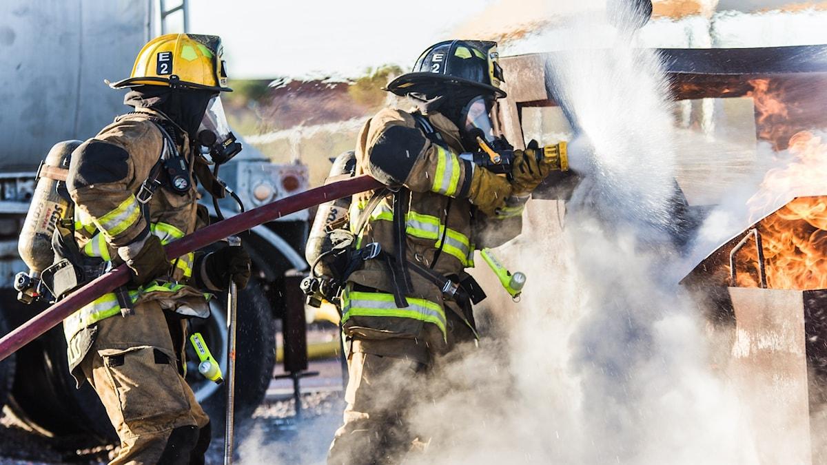 Två brandmän som släcker en eld.