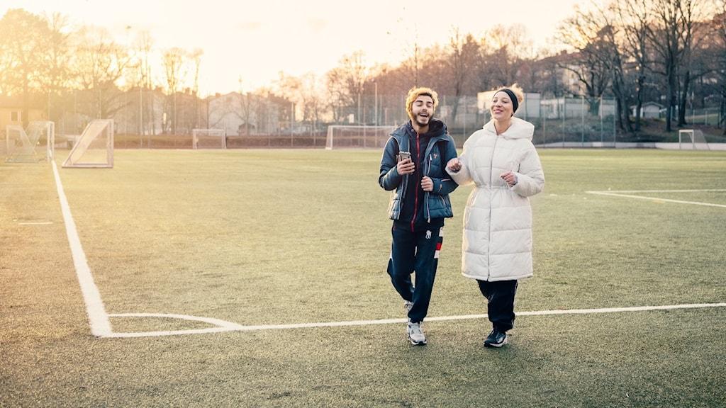 Två personer går på en fotbollsplan
