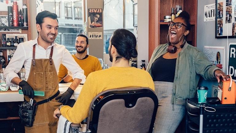 Tre personer skrattar på en frisörsalong.