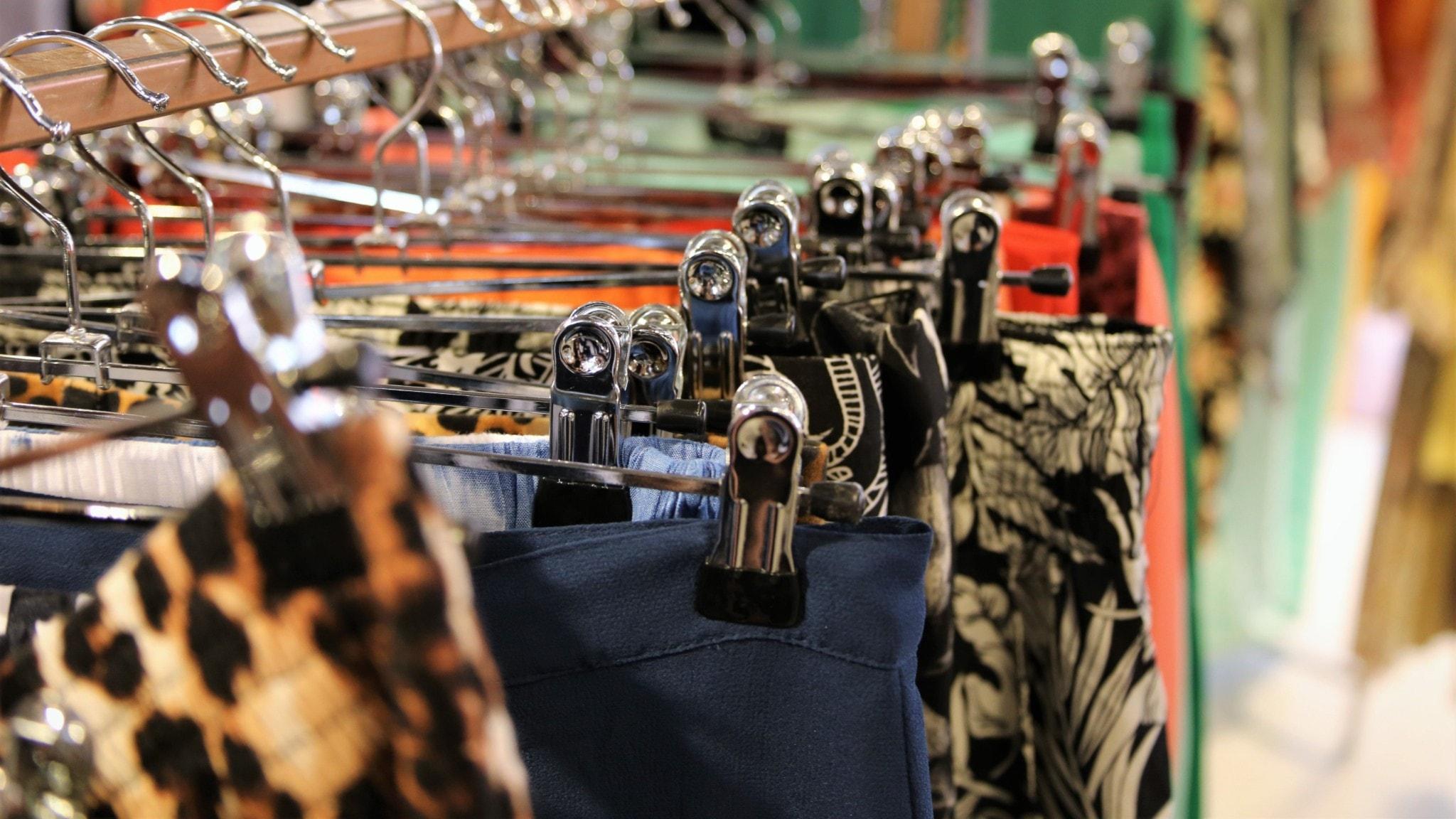 Kjolar i olika färg och mönster upphängda på galge i en butik.