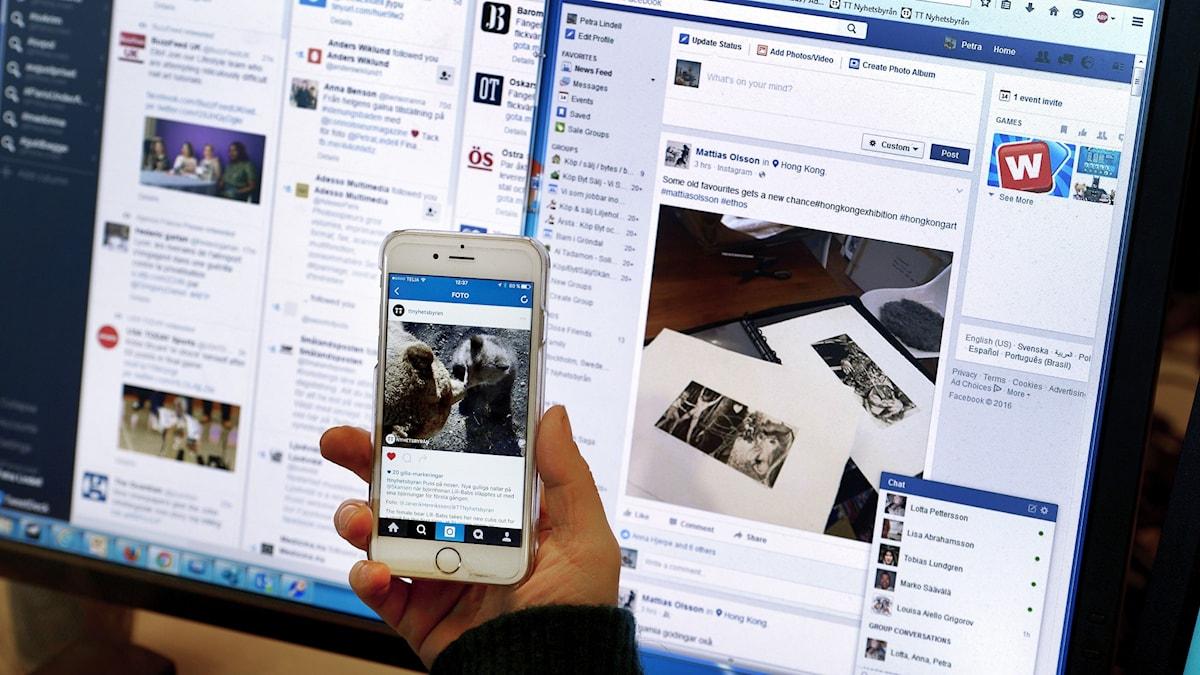 En datorskärm och en hand som håller i en mobiltelefon.
