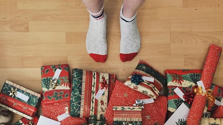 julklappar under julgran, ett par fötter i strumpor