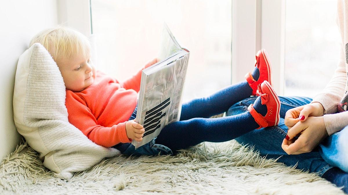 Barn sitter på en filt vid ett fönster och läser en bok.