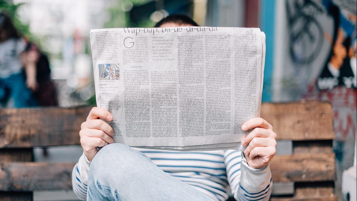 en person sitter på en parkbänk och läser en tidning