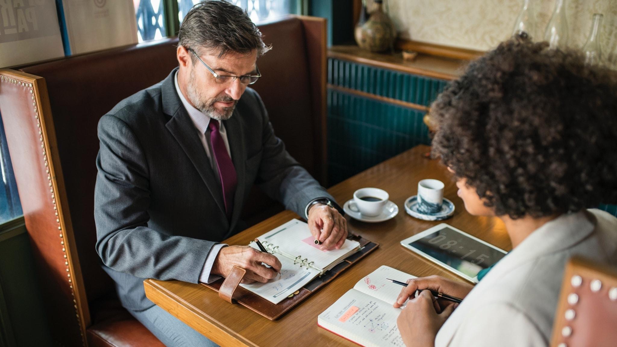 En man och en kvinna sitter mittemot varandra och planerar.