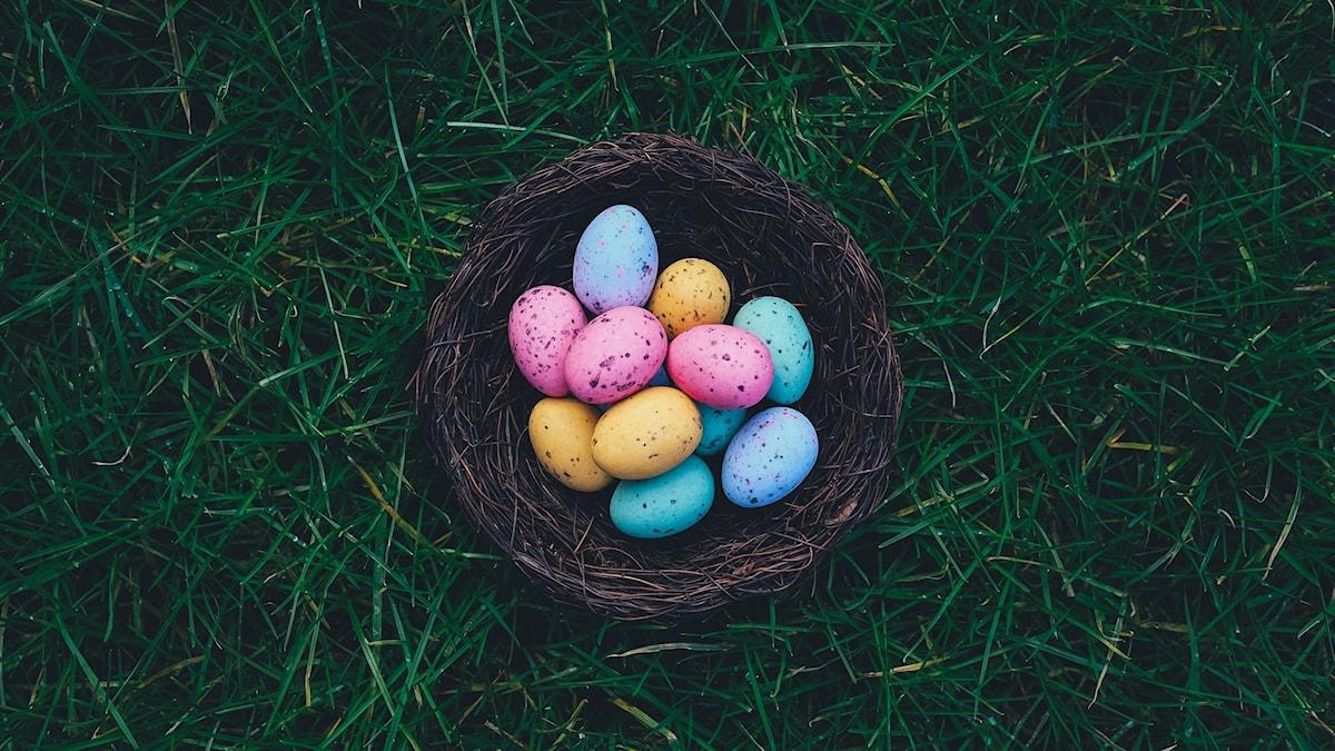 ägg i olika färger i en brun korg på gräs.