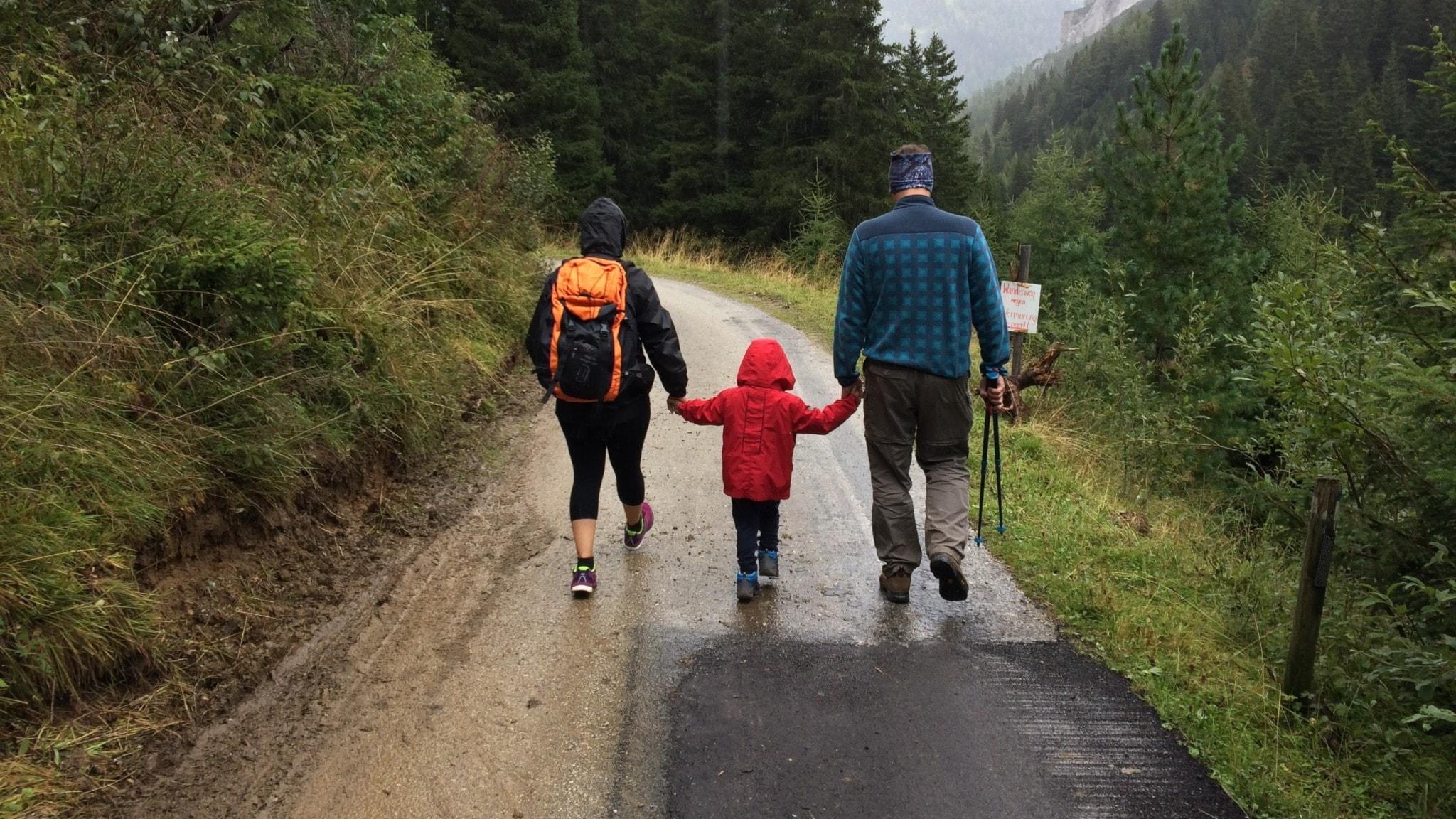 Familj på promenad längs en skogsväg.
