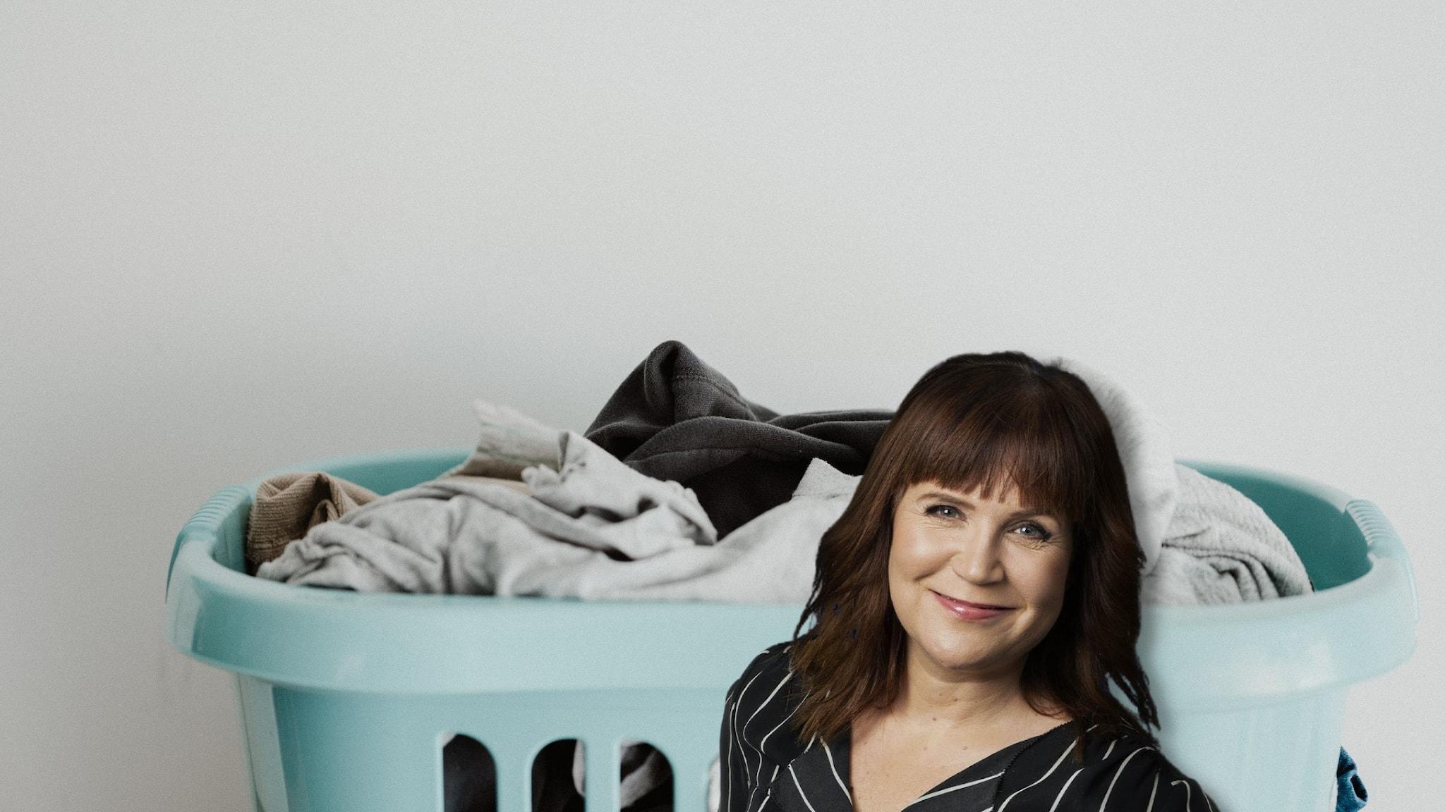 Kim Kärnfalk står framför en babybkå tvättkorg med otvättade kläder.
