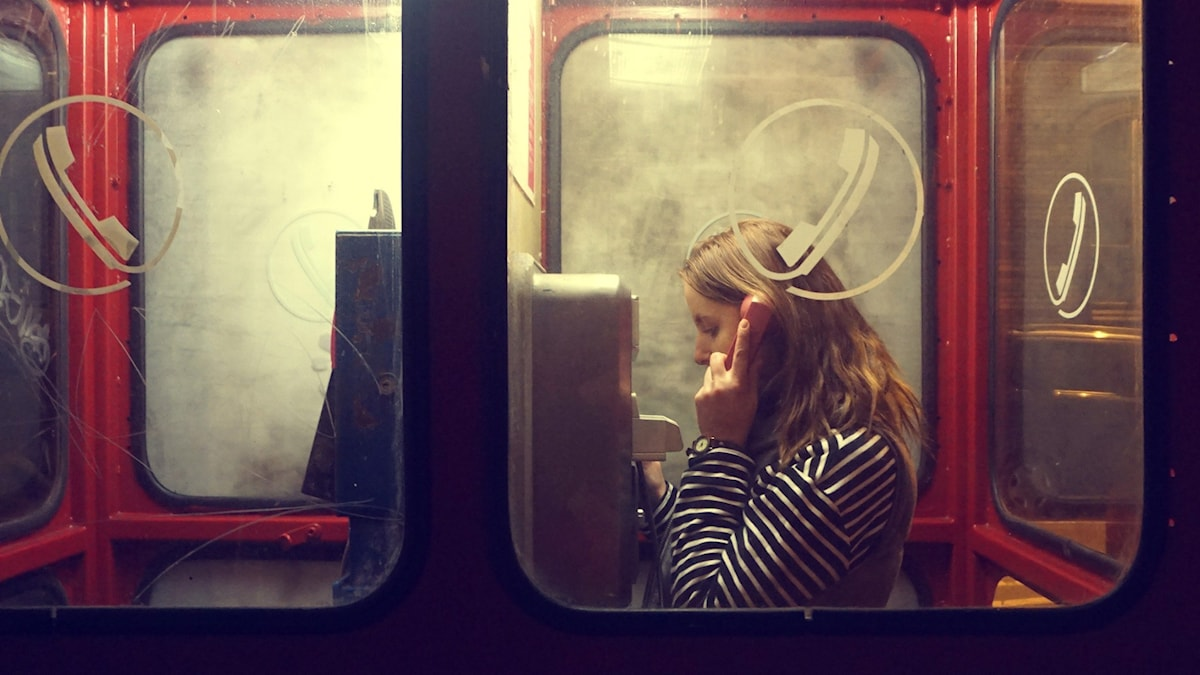 Kvinna pratar i telefon i röd telefonkiosk.