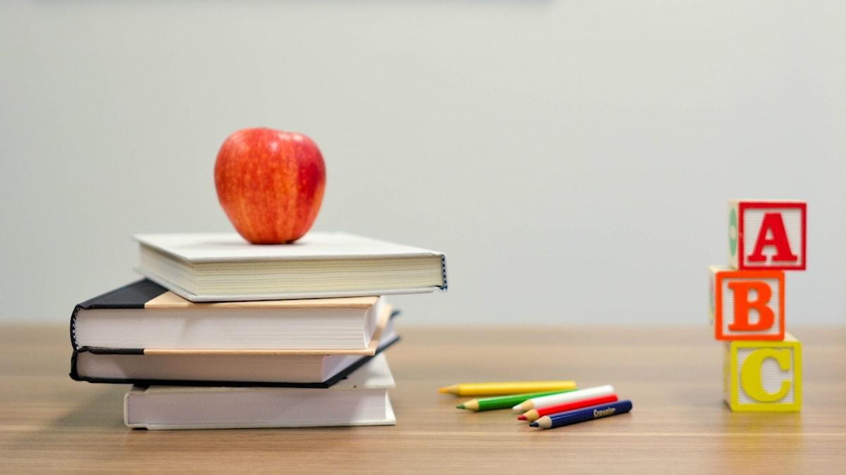 Bild på tre skolböcker, pennor och byggklossar ABC.