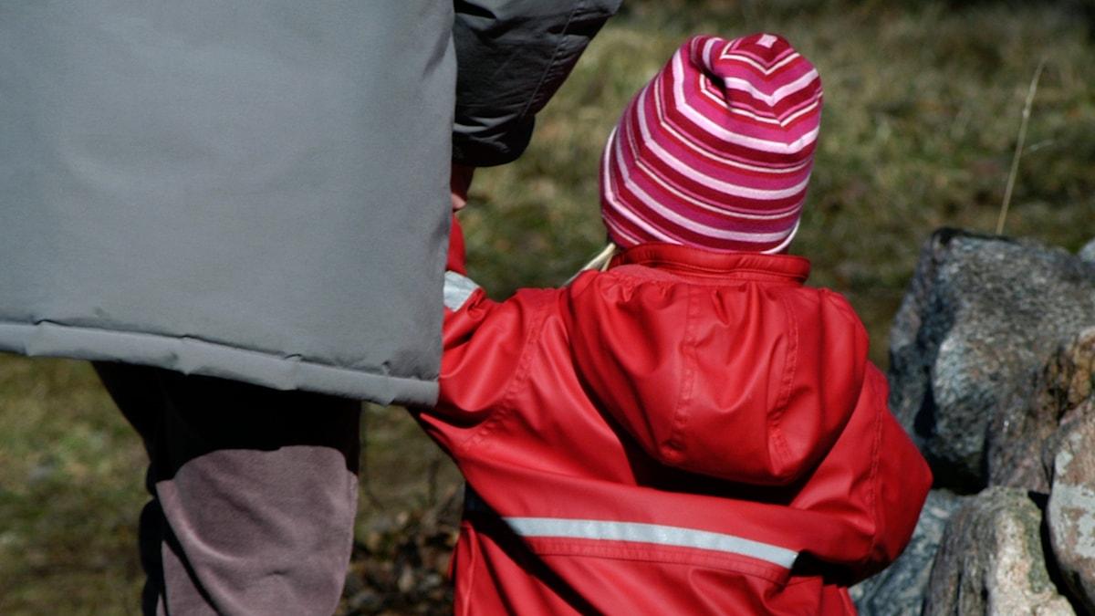 Ett barn i röd jacka håller hand med en vuxen person
