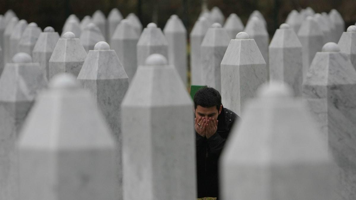 Faruk Hasanovic ber vid graven av en familjemedlem som dog i Srebrenica. Foto: AP Photo/Amel Emric/TT