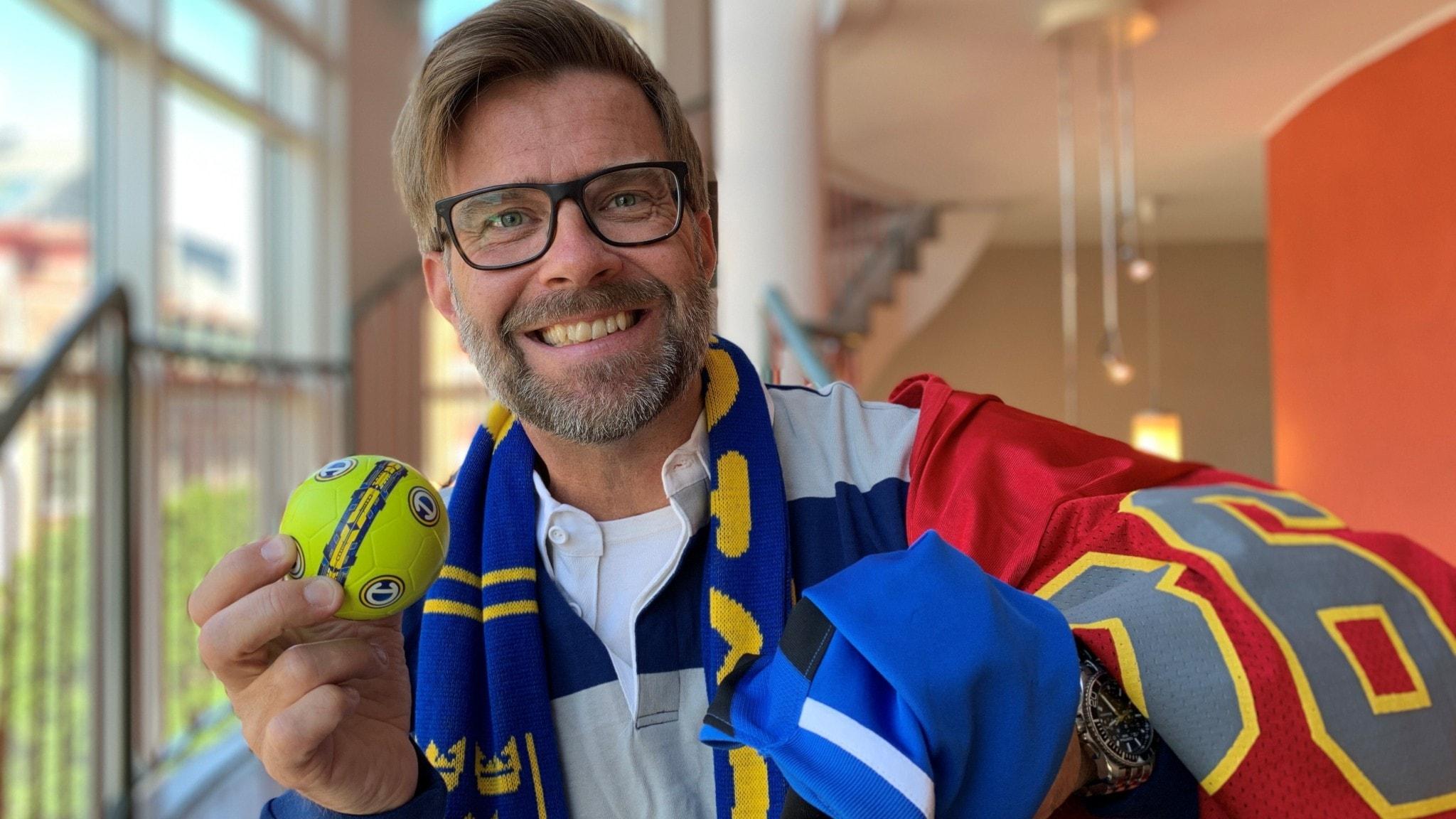 Man håller i en liten gul boll och har en Sverige-halsduk runt halsen. Står i ett trapphus.