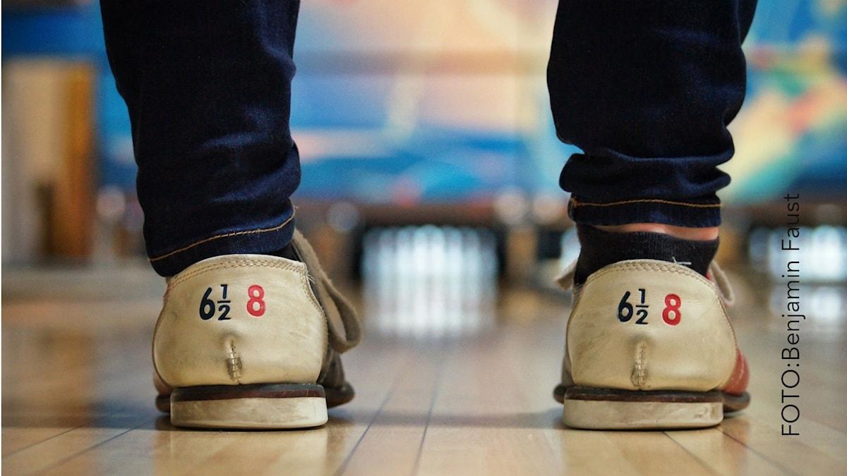 två bowlingskor och i bakgrunden käglor