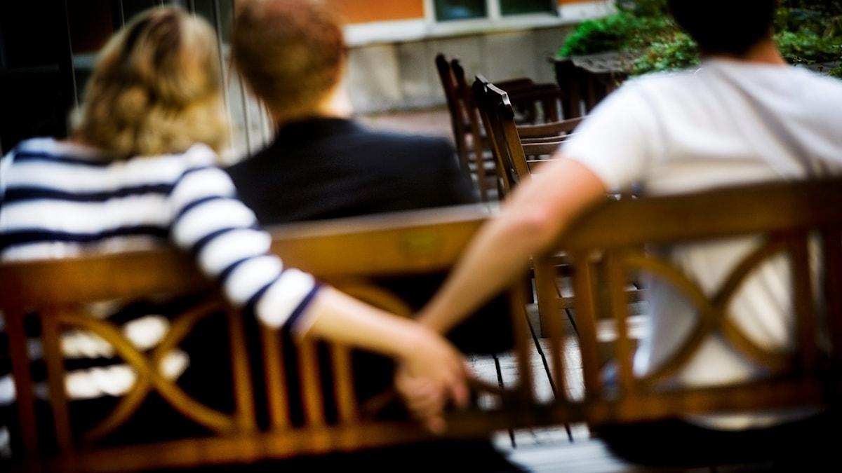 En man och en kvinna sitter på en bänk. Kvinna håller en tredje persons hand bakom ryggen.