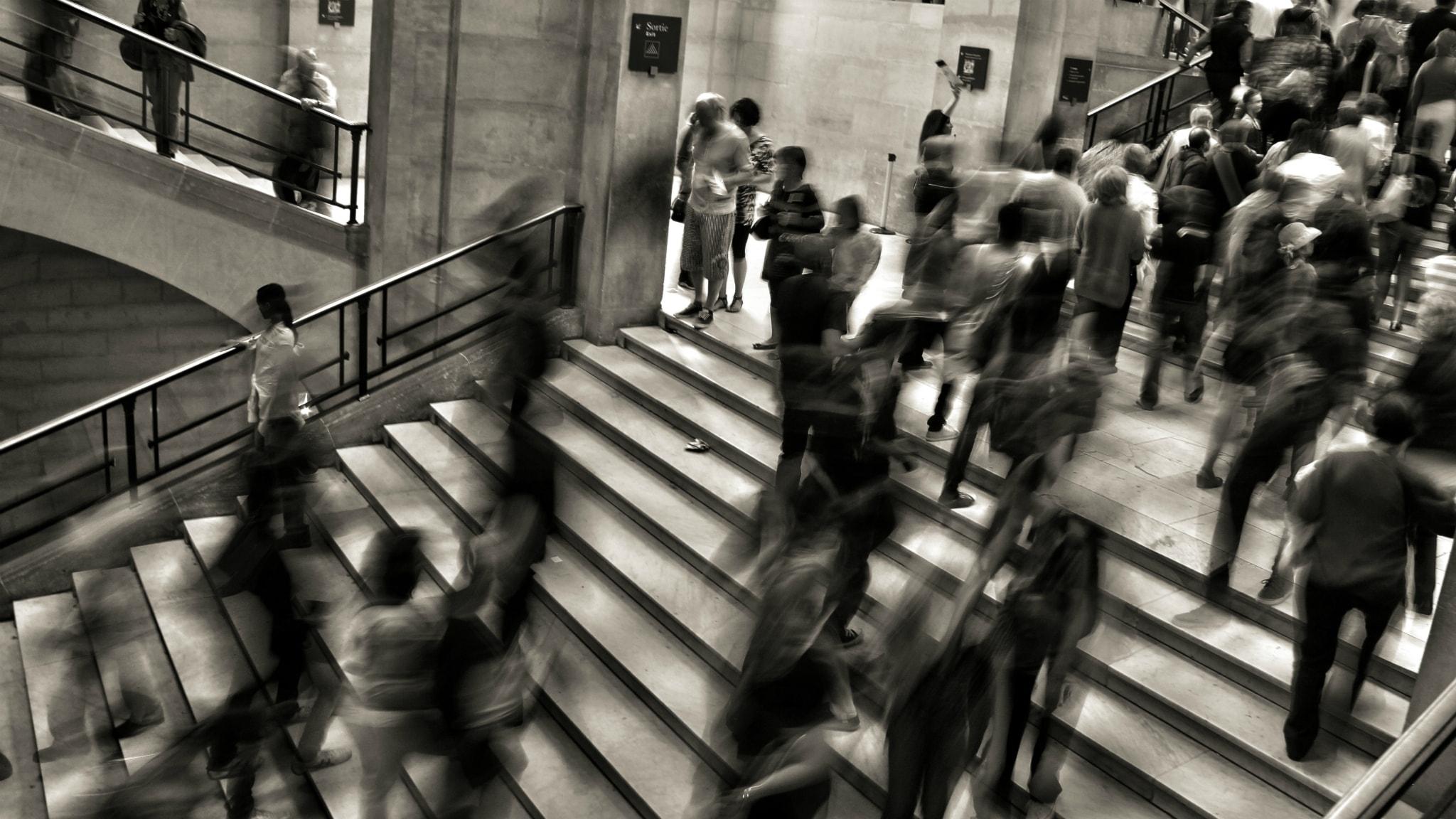 Rusning på tunnelbanan. Många människor i trappor.