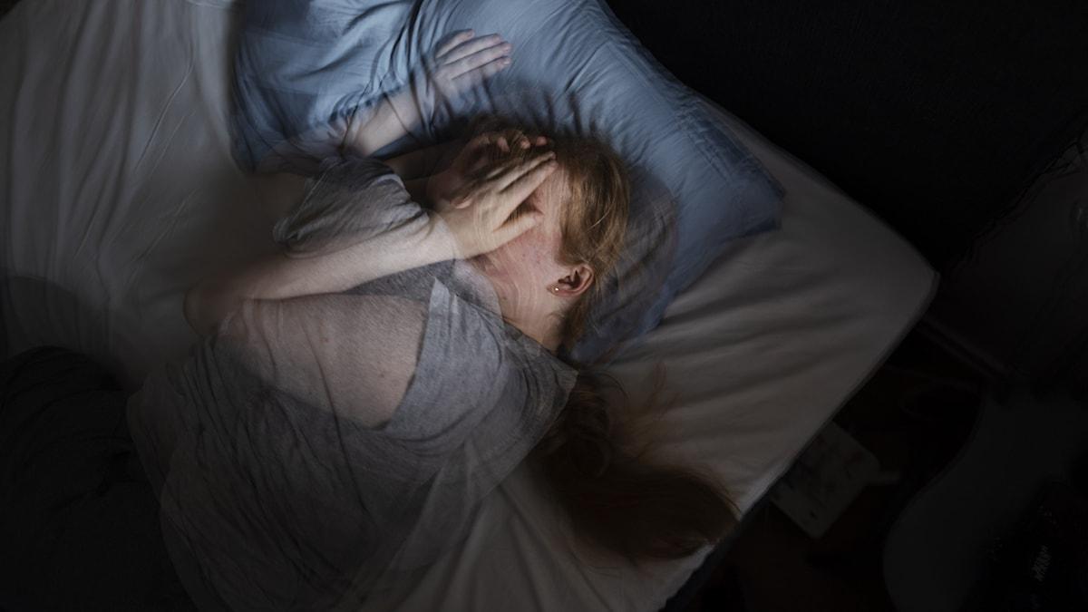 En kvinna ligger i en säng och har svårt att sova.