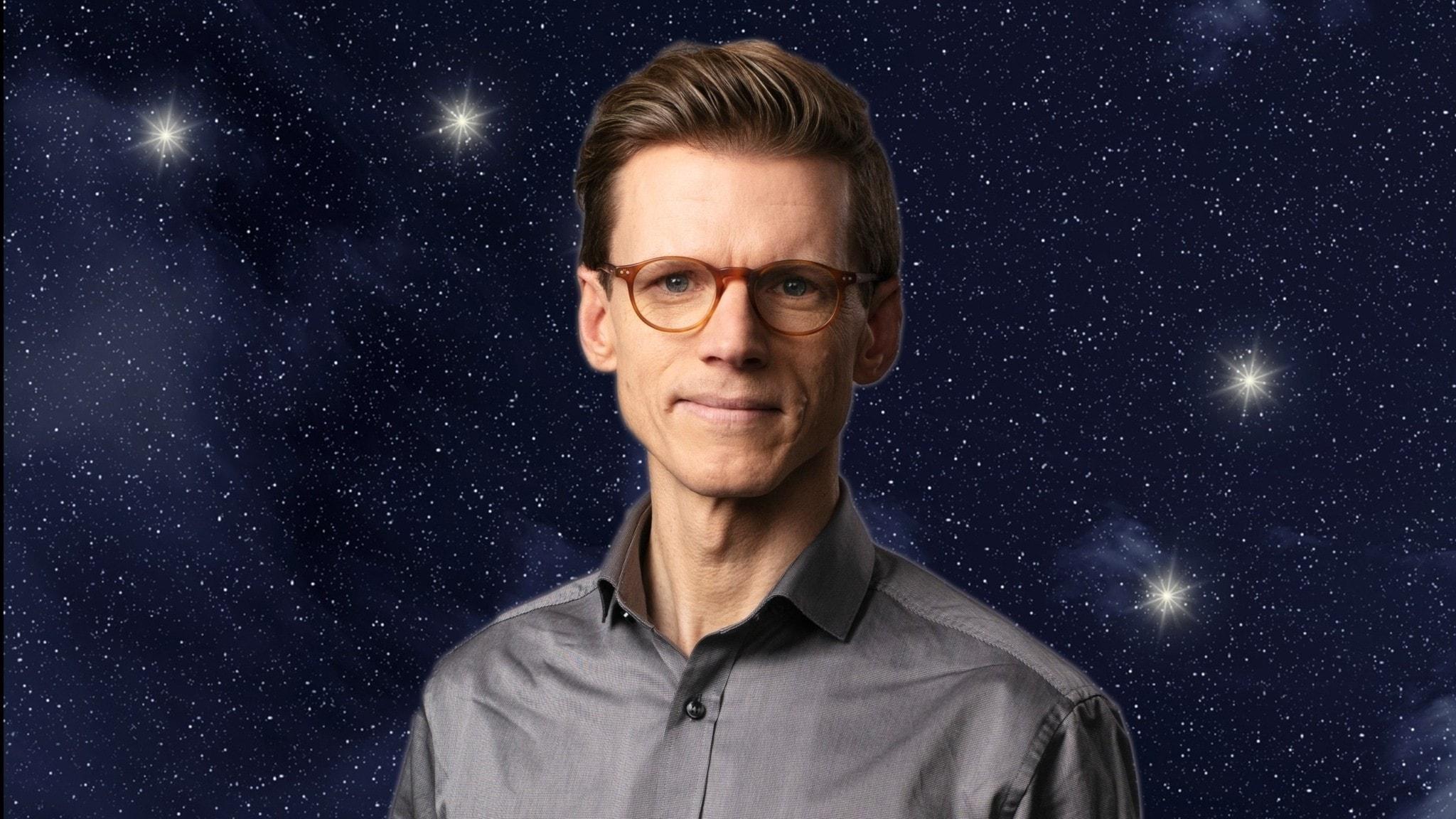 Programledare Johan Signert i grå skjorta och med bruna glasögon mot en stjärnhimmel med stjärnbilden Karlavagnen.