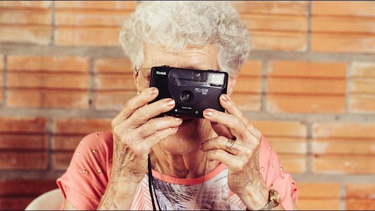 Porträtt av en vithårig, äldre dam som håller upp en kamera framför ansiktet.