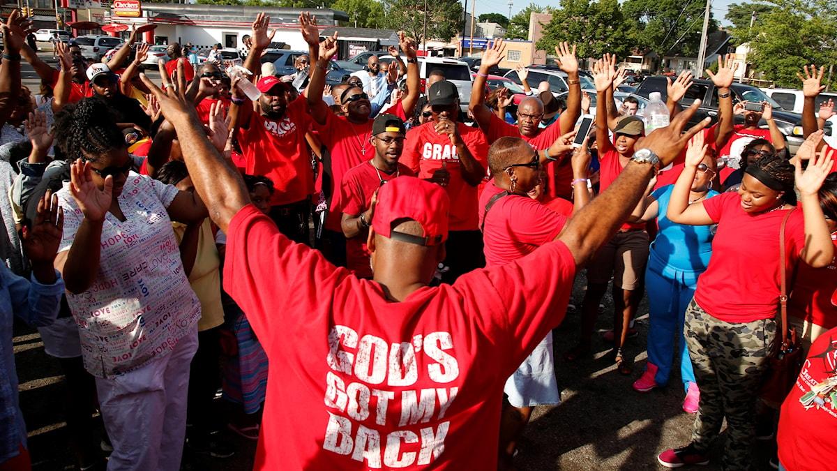 """Amerikaner ber i grupp efter en polisskjutning. I förgrunden en man med en tröja med texten :""""God's got my back"""" - Gud har min rygg."""