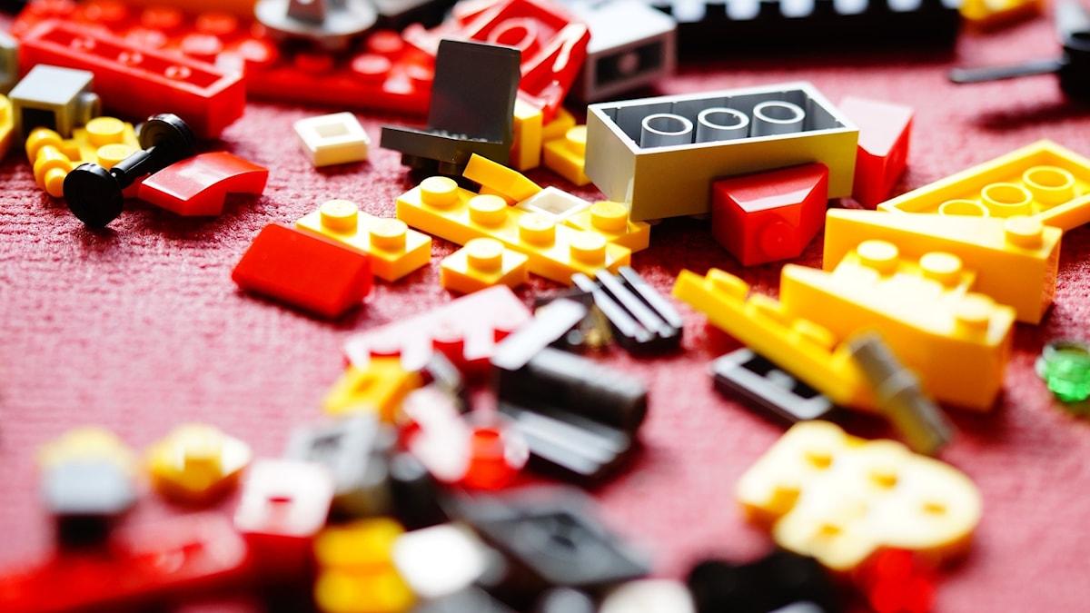 Färgglada Legobitar på ett golv