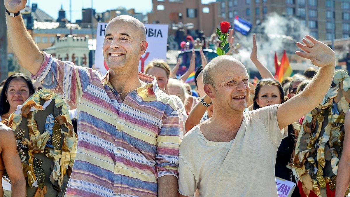 """Mark Levengood och Jonas Gardell marscherar i pridetåget. Paret är kanske ett exempel på att teorin om """"ärliga finnar och hövliga svenskar"""" inte stämmer."""