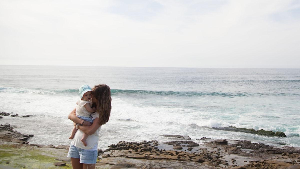 Mamma och barn vid hav.