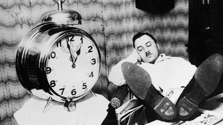 Svartvitt fotografi på världen största väckarklocka, med en man som sitter bredvid och sover i en stol med fötterna på skrivbordet.