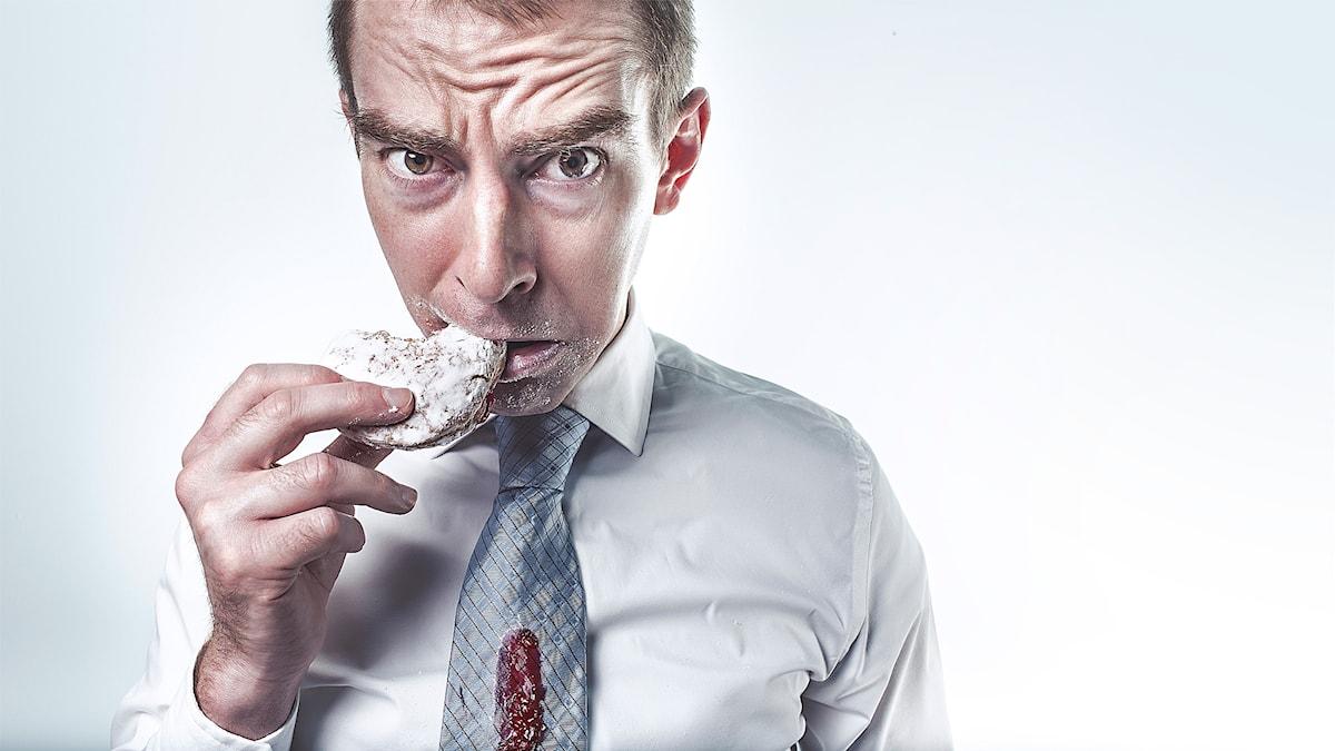 En man med en oroad uppsyn mumsar på en sockrig syltmunk. Han har florsocker runt munnen och sylt på slipsen.