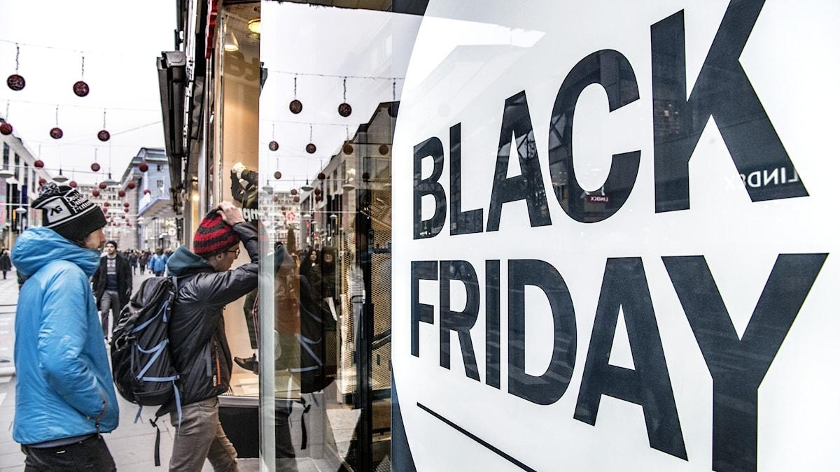 """Skyltfönster med texten """"Black Friday"""", människor på väg in i butiken."""