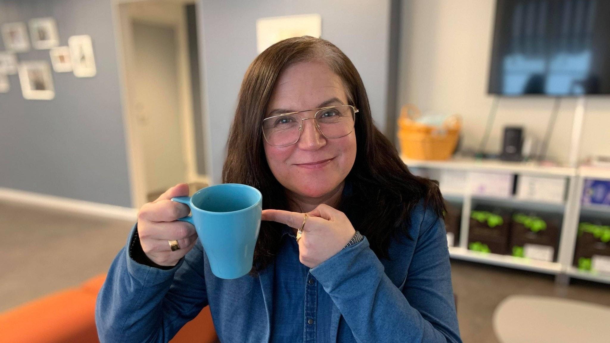 kim kärnfalk med en kaffekopp i handen
