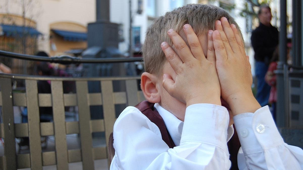 Litet barn som gömmer ansiktet i händerna