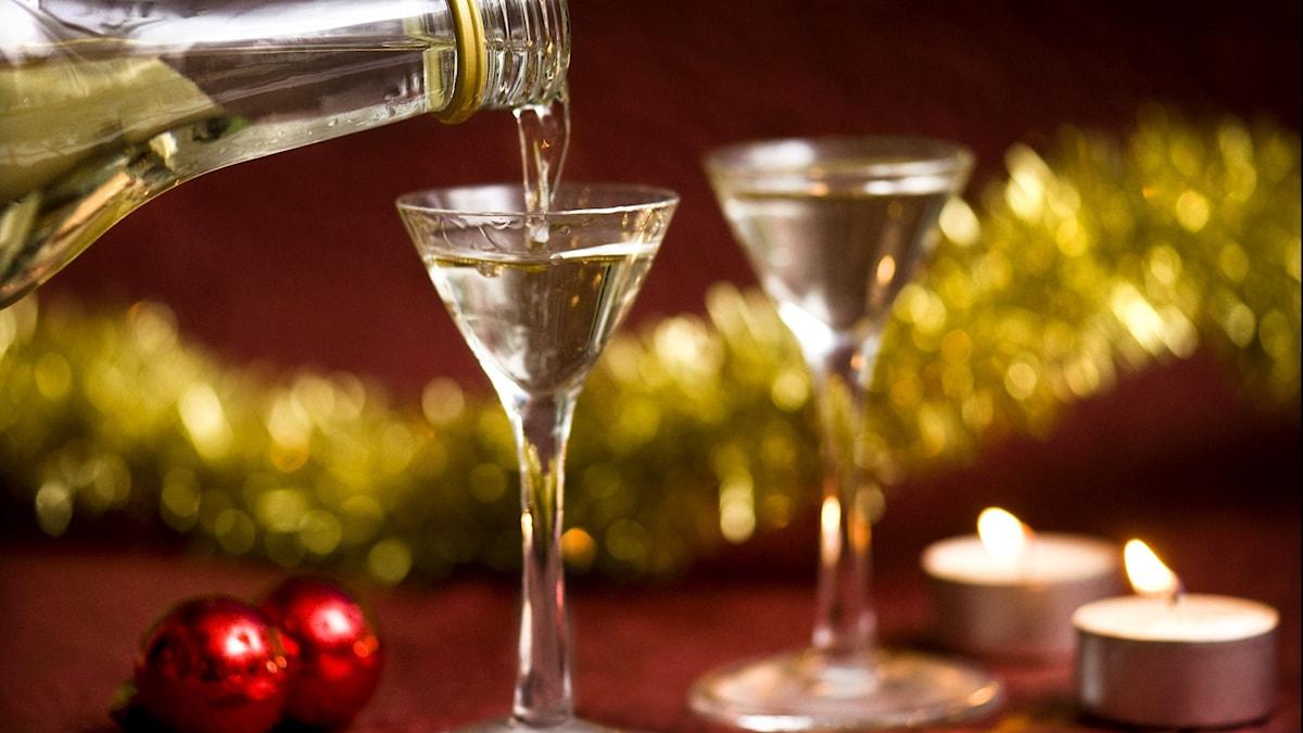 Två glas med snaps på ett bord med ljus och juldekorationer. Vätska från en flaska hälls i ett av glasen.