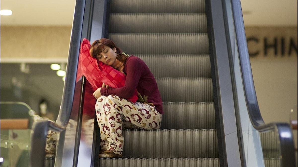 en person sitter och sover i en rulltrappa
