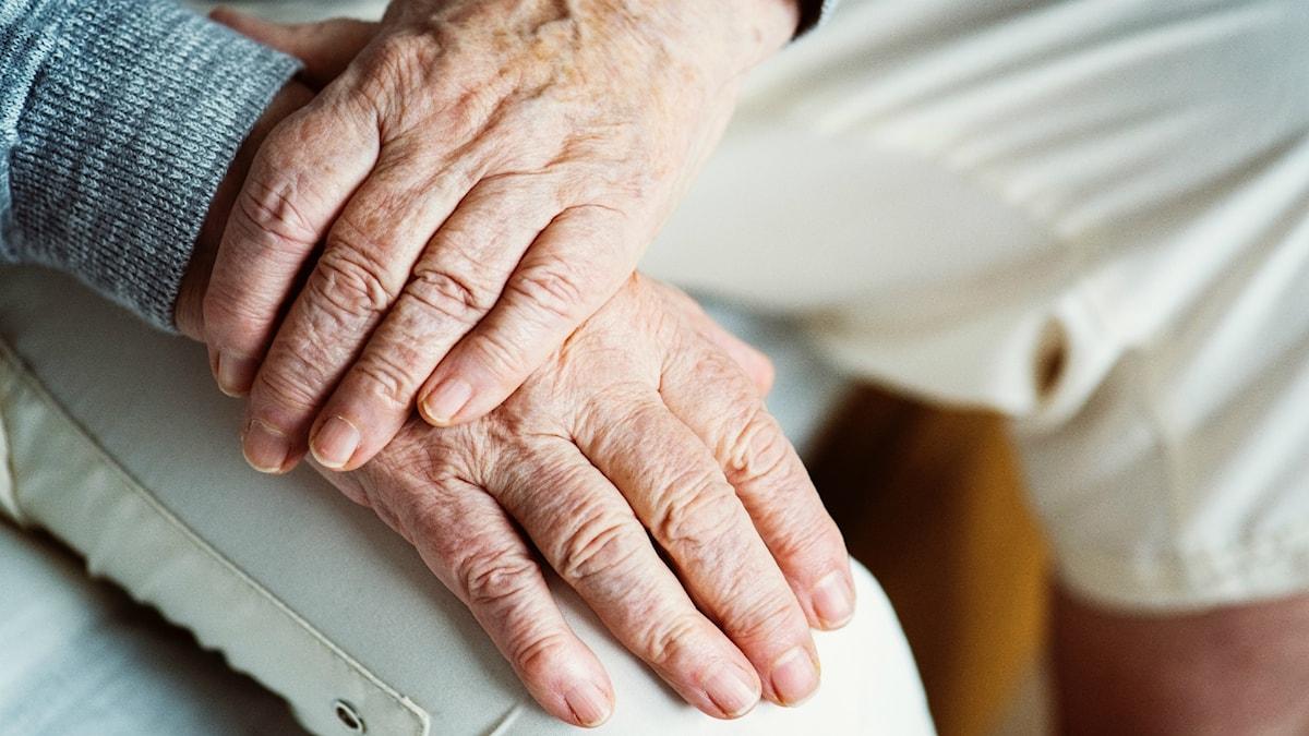 Äldre vit man lägger ena handen på den andra som vilar på knät.